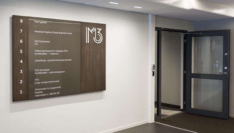 Innedørskilt, informasjonskilt, skilt, skilt på vegg inne. Skilt i kontorlandskap.
