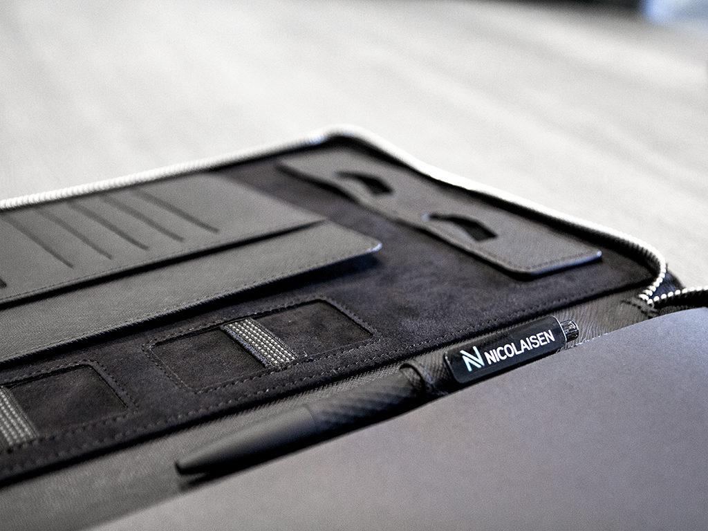 Dokumentmappe og penn med firmalogo.