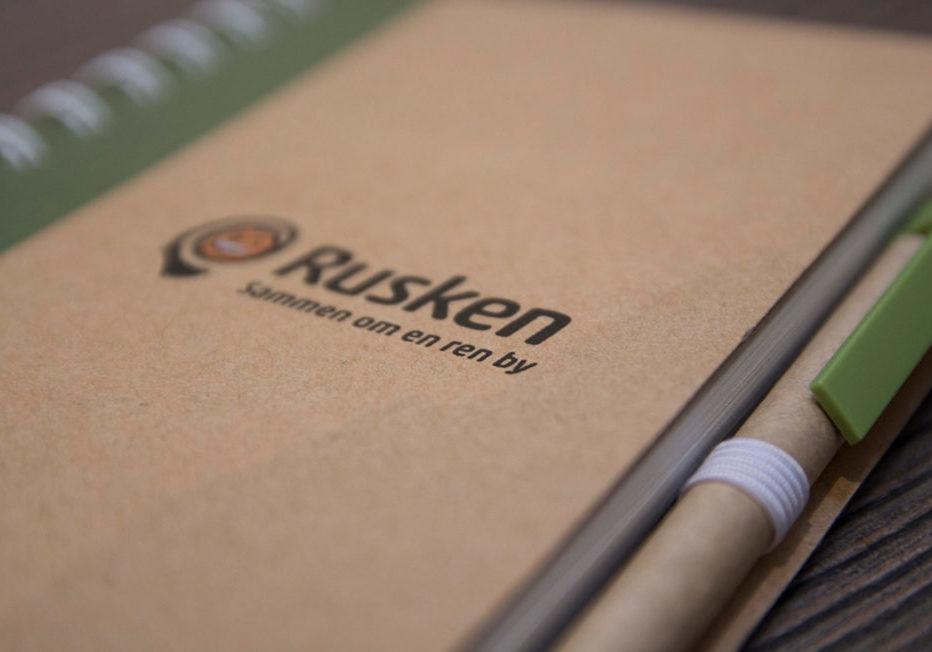 Profilartikler, profilklær og profilgaver til Oslo kommune Rusken. Notatbok miljøvennlig Rusken, notatbok med penn, resirkulert papp