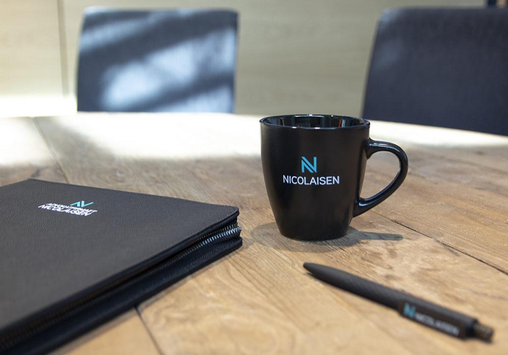 profilartikler Avdokatfirmaet Nicolaisen. Dokumentmappe, penn og krus med firmalogo.
